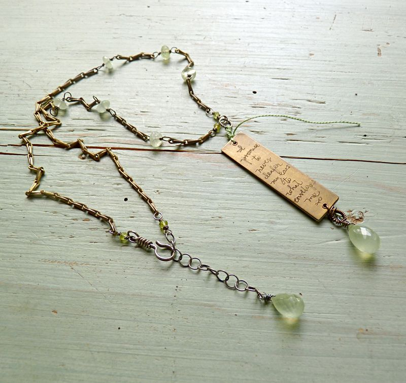 Prologue green necklace with charm on table